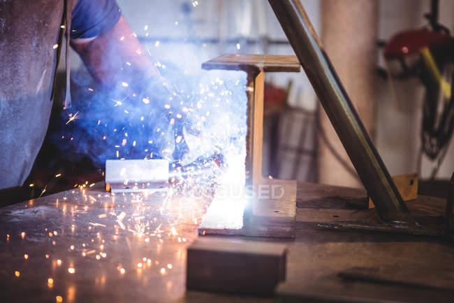 Cropped image of welder welding metal in workshop — Stock Photo