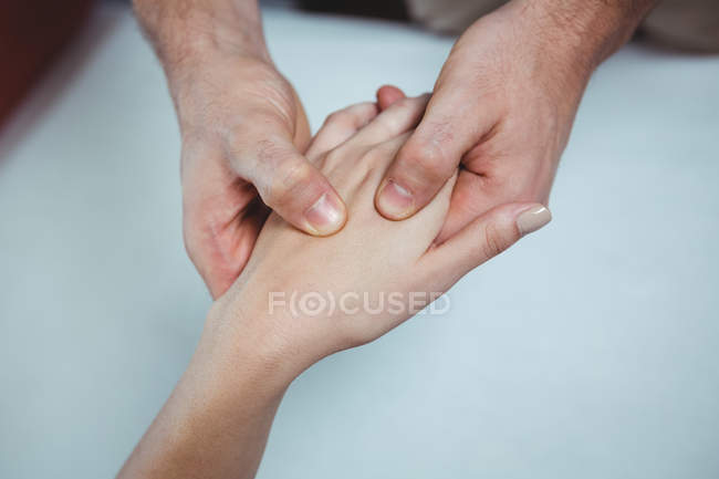 Cropped image of physiotherapist massaging hand of female patient in clinic — Stock Photo