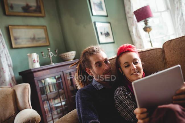Jovem casal usando tablet digital no sofá em casa — Fotografia de Stock