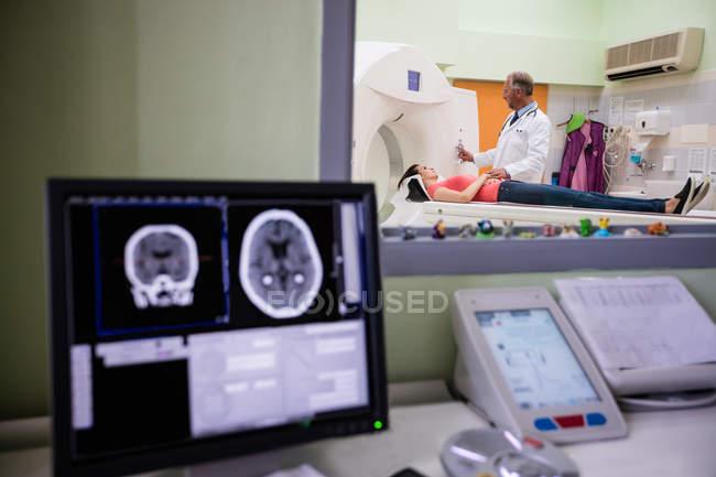 Exploración cerebral digital en el monitor de la computadora con escáner de resonancia magnética en segundo plano - foto de stock