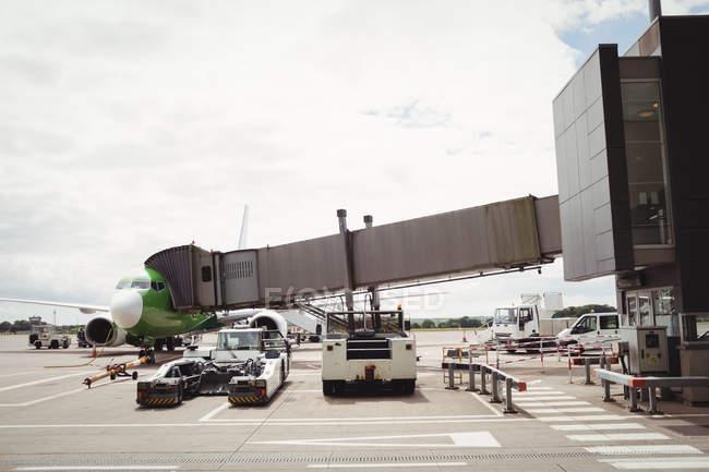 Avião com ponte de carregamento se preparando para partida no terminal do aeroporto — Fotografia de Stock