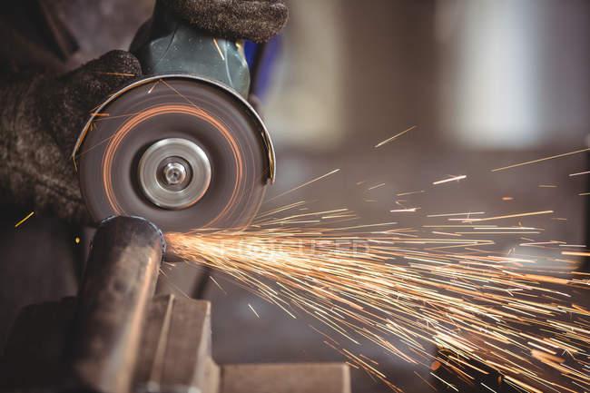 Imagem cortada de soldador serrar metal com ferramenta elétrica na oficina — Fotografia de Stock