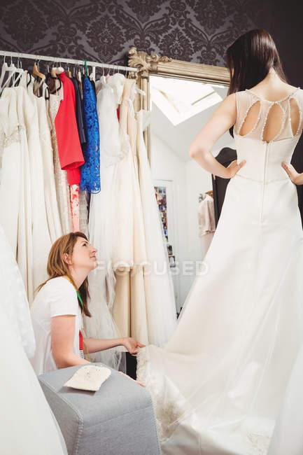 Жінка приміряє Весільне плаття в студії з допомогою творчих дизайнера — стокове фото
