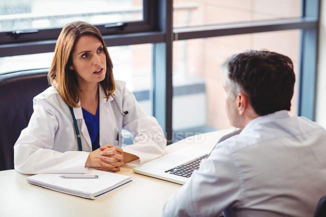 Médico na mesa conversando com o paciente no hospital — Fotografia de Stock