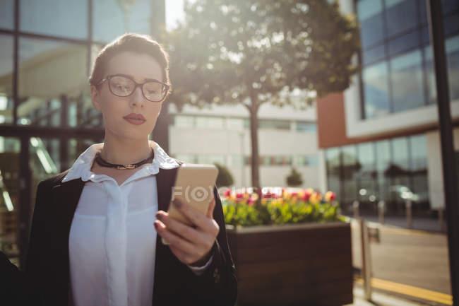 Jeune femme utilisant le téléphone mobile par la construction — Photo de stock