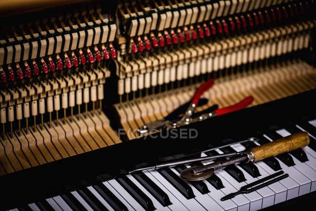 Nahaufnahme von Reparaturwerkzeugen auf alter Klaviertastatur in der Werkstatt — Stockfoto