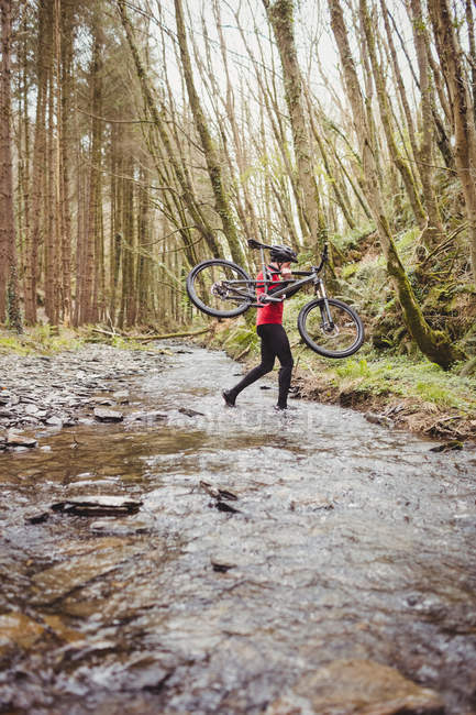 Side view of biker carrying bicycle while crossing stream in forest — Stock Photo