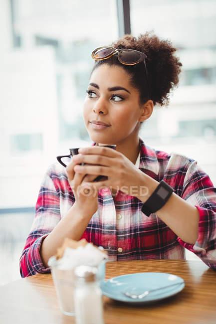 Продуманий жінки, що тримає чашку кави, сидячи за столом у ресторані — стокове фото