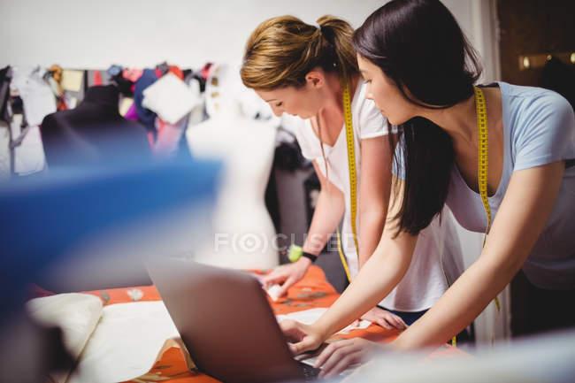 Жіноча мода дизайнерів, що працюють на ноутбуці в студії — стокове фото