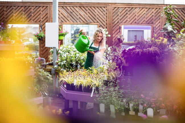 Female florist watering plants with watering can in garden centre — Stock Photo