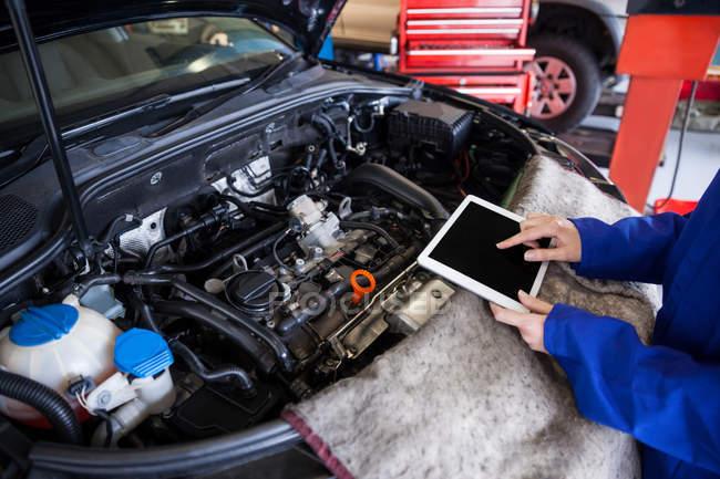Обітнутого зображення механік, використовуючи цифровий планшетний при обслуговуванні двигуні автомобіля на ремонт гаража — стокове фото