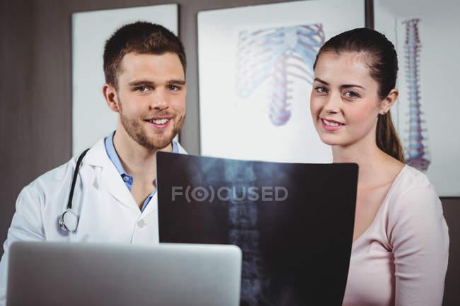 Retrato de fisioterapeuta explicando raio-X da coluna vertebral para paciente do sexo feminino na clínica — Fotografia de Stock