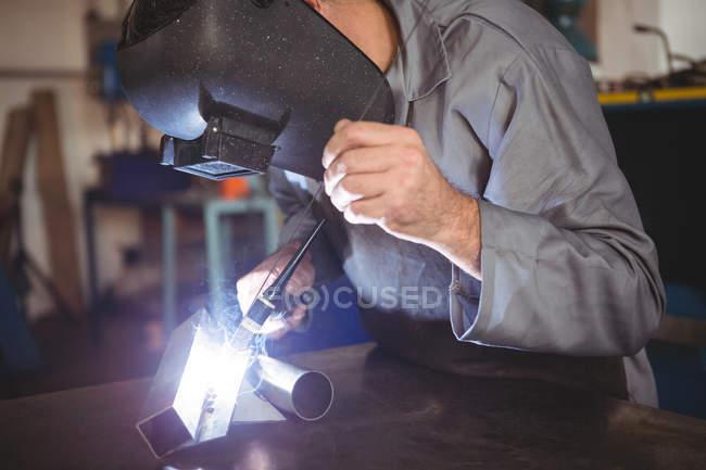 Welder working on piece of metal in workshop — Stock Photo