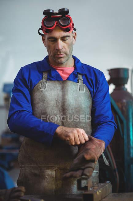 Male welder wearing glove in workshop — Stock Photo