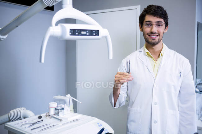 Portrait of smiling dentist standing with a dental tools at dental clinic — Stock Photo