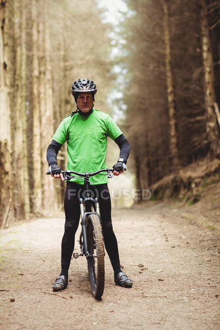 Front view of mountain biker standing on dirt road in forest — Stock Photo