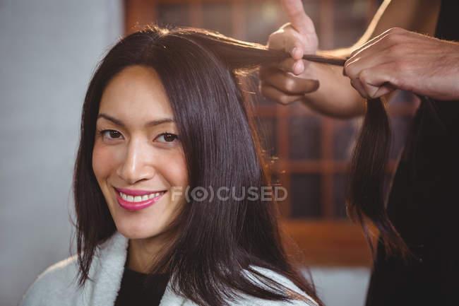 Parrucchiere che lavora su cliente sorridente a salone di capelli — Foto stock
