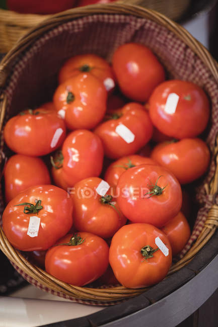 Close-up of fresh tomatoes in wicker basket at supermarket — Stock Photo