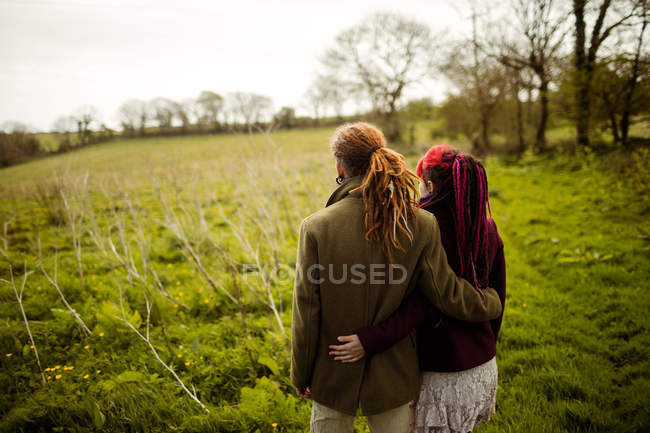 Rear view of hipster couple with arm around while standing in park — Stock Photo