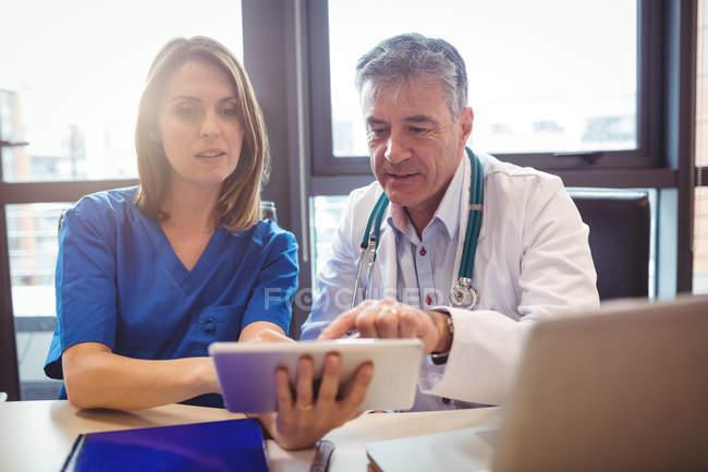 Врач обсуждает с медсестрой цифровые таблетки в больнице — стоковое фото
