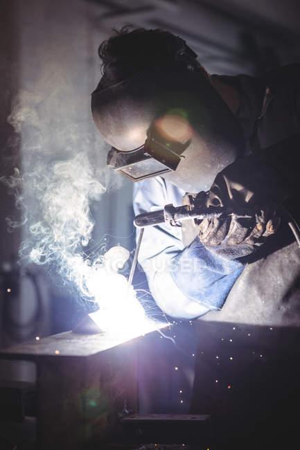 Welder welding metal in workshop — Stock Photo