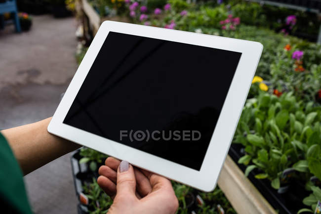 Cropped image of Female florist using digital tablet at garden centre — Stock Photo