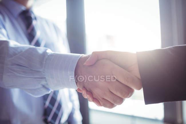 Кадроване зображення бізнесмен потискують один одному руки з колегою в офісі — стокове фото