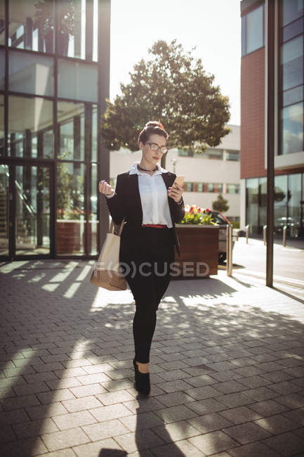 Full length of young businesswoman walking on street — Stock Photo