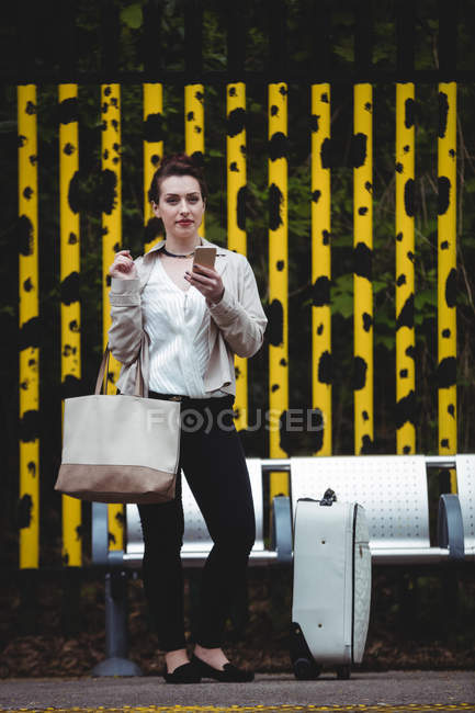 Pretty woman standing against fence at railroad station platform — Stock Photo