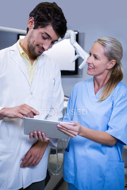 Dentist and dental assistant working together on tablet at dental clinic — Stock Photo