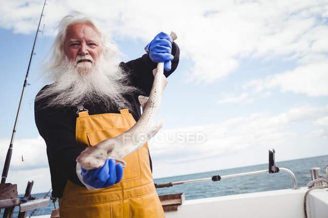 Porträt eines Fischers, der Fisch auf dem Boot hält — Stockfoto