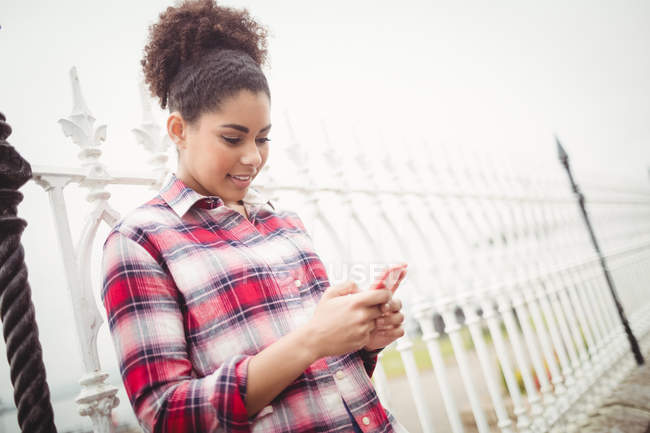 Pretty young woman using phone while leaning on railing — Stock Photo