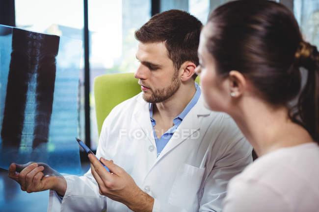 Physiotherapist explaining spine x-ray to female patient in clinic — Stock Photo