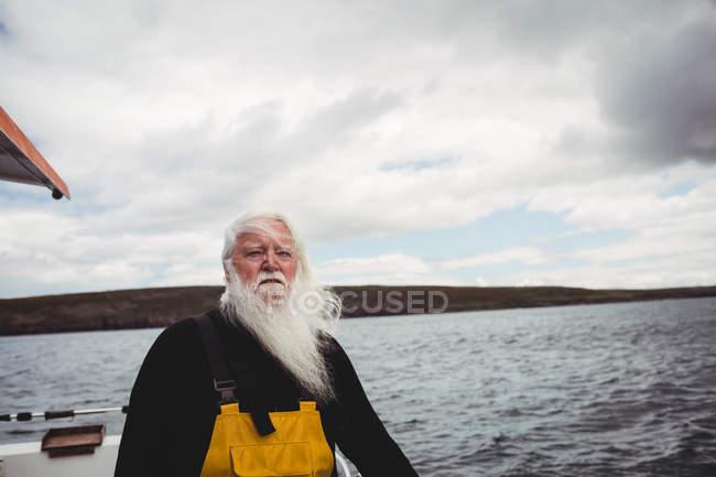 Nachdenklicher Fischer, der vom Fischerboot auf das Meer blickt — Stockfoto
