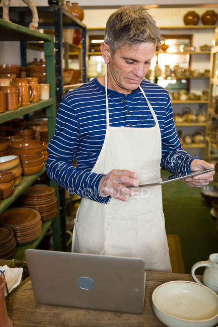 Männliche Potter mit digital-Tablette mit Laptop auf der Arbeitsplatte in der Keramikwerkstatt — Stockfoto