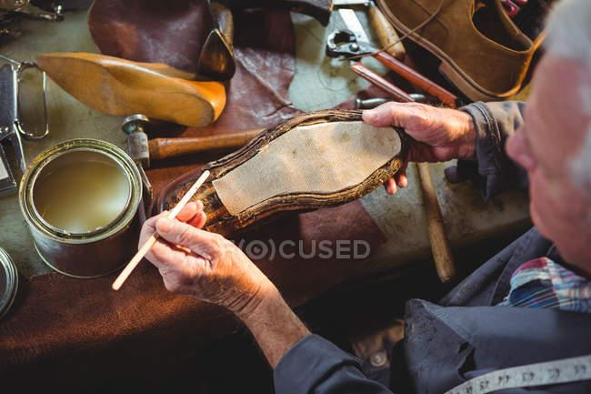 Visão aérea do sapateiro aplicando cola na sola do sapato na oficina — Fotografia de Stock