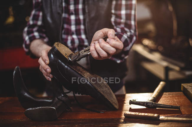 Mid section of male shoemaker repairing a shoe in workshop — Stock Photo