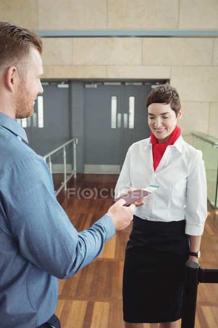 Empresario mostrando su tarjeta de embarque en el mostrador de facturación en el aeropuerto - foto de stock