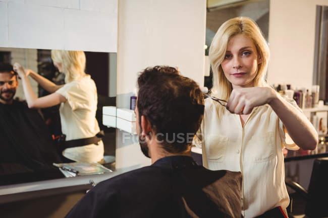 Hairdresser trimming client hair at hair salon — Stock Photo