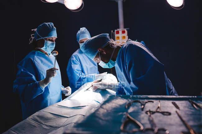 Cirujanos realizar operación en sitio de operación en el hospital - foto de stock
