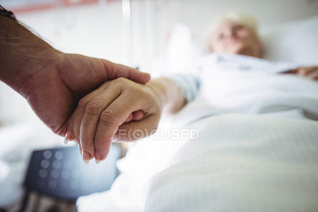 Senior man holding hands of senior woman in hospital — Stock Photo