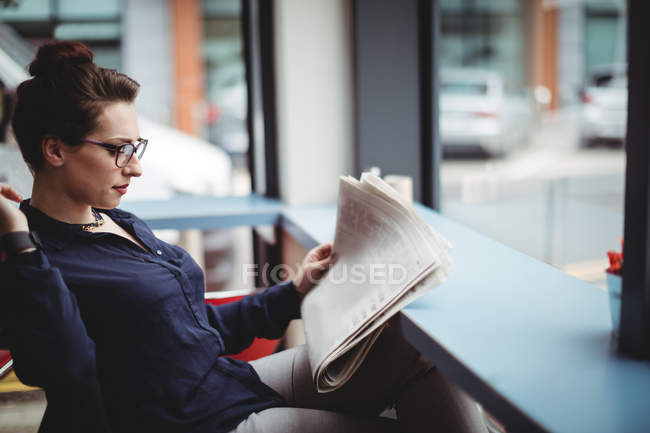 Businesswoman reading newspaper in cafe — Stock Photo