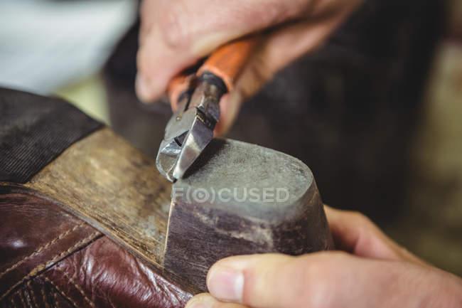 Hands of shoemaker repairing a shoe in workshop — Stock Photo