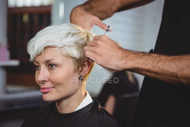 Smiling female getting her hair trimmed at salon — Stock Photo