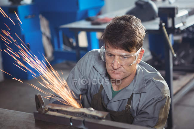 Handsome welder cutting metal with electric tool in workshop — Stock Photo
