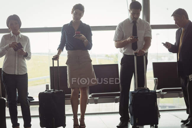 Business people using mobile phones in waiting area — Stock Photo