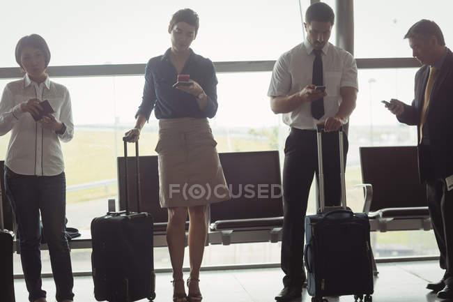 Pessoas de negócios usando telefones móveis na sala de espera — Fotografia de Stock