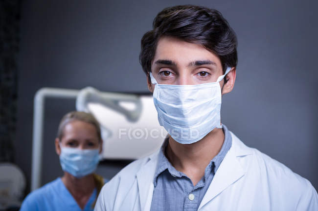 Portrait of dentist and dental assistant wearing surgical masks at dental clinic — Stock Photo