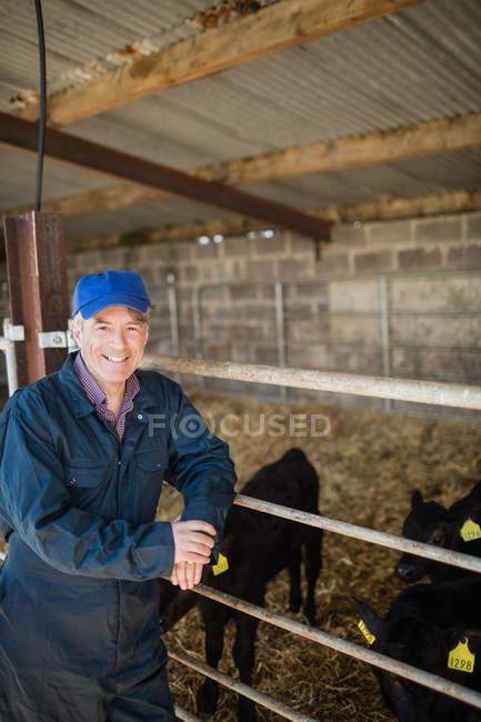 Porträt eines glücklichen Landarbeiters, der am Zaun eines Schuppens steht — Stockfoto
