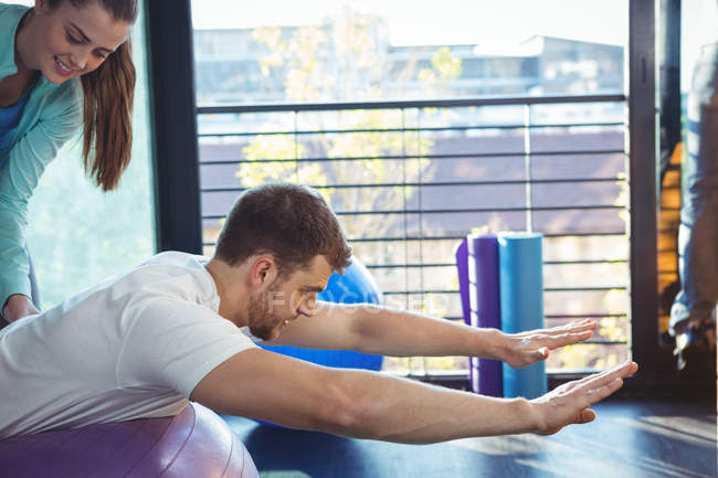 Female physiotherapist helping male patient on exercise ball in clinic — Stock Photo